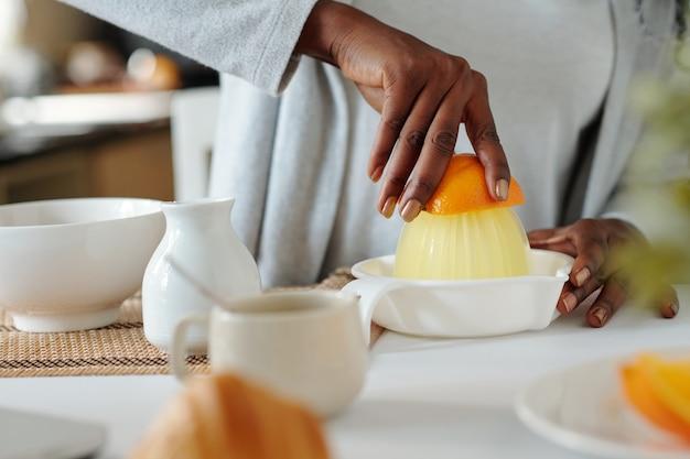 Handen van een vrouw die een handmatige sapcentrifuge gebruikt bij het maken van een vers sinaasappeldrankje op het aanrecht