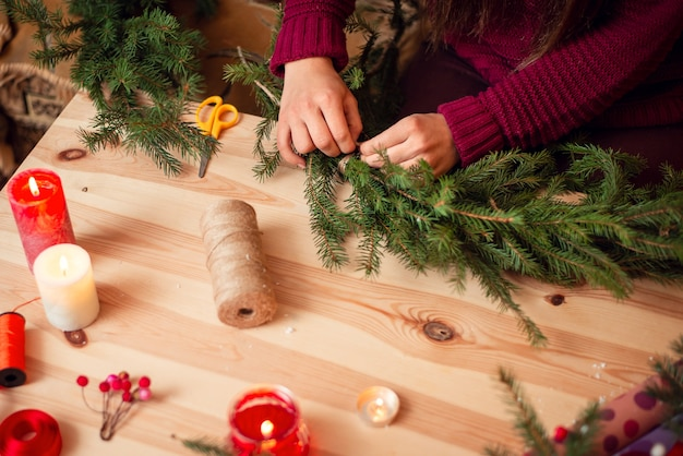 Handen van een vrouw die een kerstkrans maakt van natuurlijke dennentakken