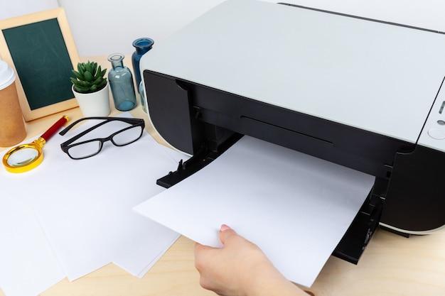 Handen van een vrouw die een kopieermachine dicht uitputten