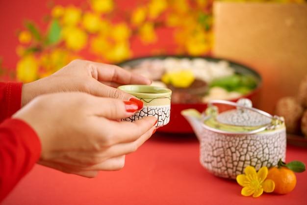 Handen van een vrouw die een kopje groene thee drinkt met zoete gedroogde vruchten op de chinese nieuwjaarsviering