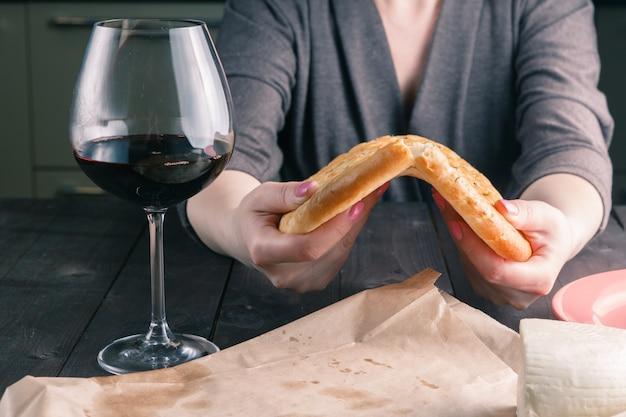 Handen van een vrouw die en brood breekt deelt