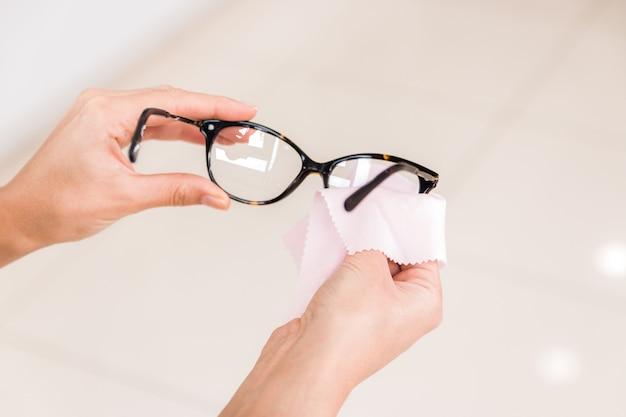 Handen van een vrouw die haar bril afveegt