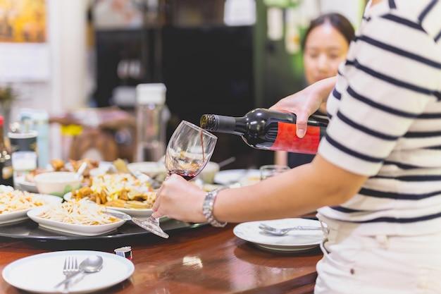 Handen van een vrouw die rode wijn in twee glazen uit een fles giet met een vrouw op de achtergrond aan de eettafel
