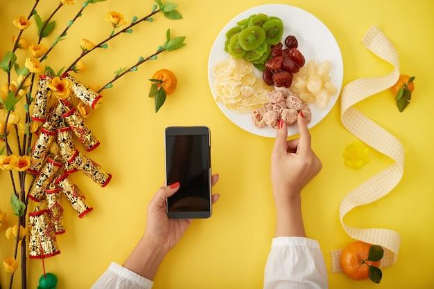 Handen van een vrouw die traditionele chinese nieuwjaarssnacks eet en sms-berichten stuurt naar haar vrienden en familieleden via smartphone