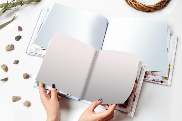Handen van een vrouw die twee open fotoboeken met harde kaft en blanco pagina vasthoudt