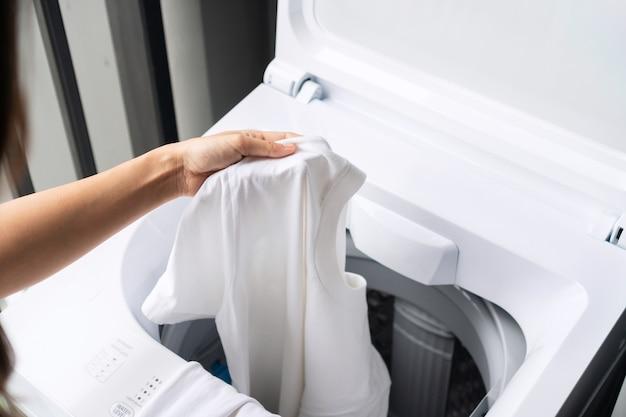 Handen van een vrouw die witte kleurkleren in de wasmachine stopt. wasconcept. bovenaanzicht