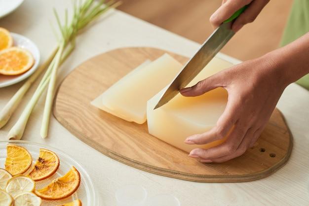 Handen van een vrouw die zeepbasis snijdt met een scherp mes bij het maken van reinigingsrepen thuis