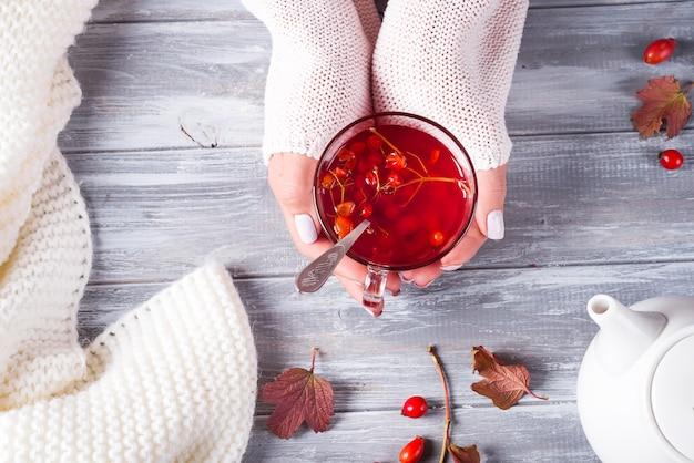 Handen van een vrouw in een trui met een kop warme thee op een grijze houten achtergrond