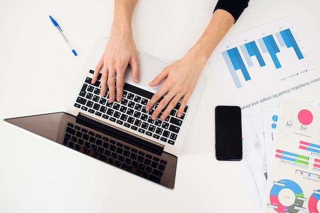 Handen van een vrouw met behulp van een laptop