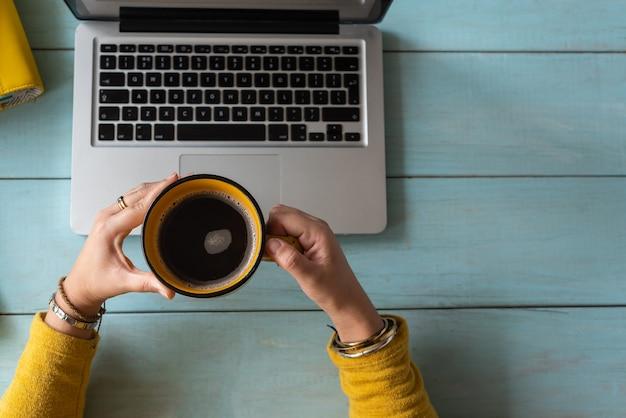 Handen van een vrouw met een kopje koffie werkten op haar laptop. werk thuis concept.