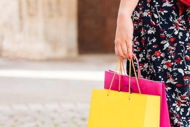 Handen van een vrouw met gekleurde tassen tijdens het winkelen in de verkoop.