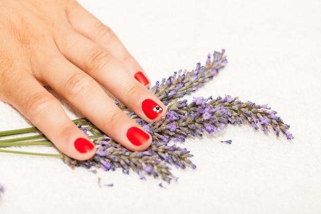 Handen van een vrouw met rood nagellak gesteld door een schoonheidsspecialiste