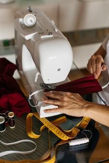 Handen van een vrouw naaien gezichtsmaskers