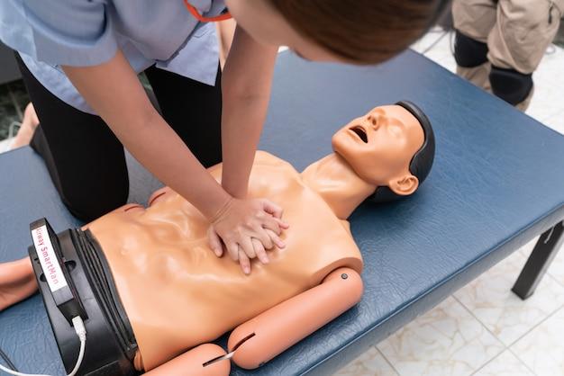 Handen van een vrouw worden gezien op een mannequin tijdens een oefening van reanimatie (cpr).