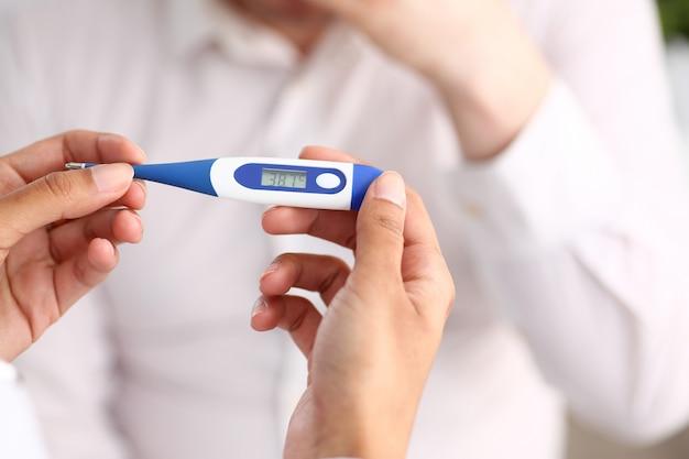 Handen van een vrouwelijke arts die een thermometer houdt