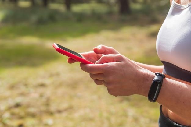 Handen van een vrouwelijke atleet die mobiele app gebruikt in fitnessles of krachttraining buitenshuis doet met activity tracker. kopieer de ruimte.