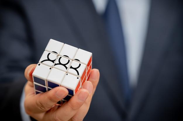 Handen van een zakenman die een kubus met een zichtbaar mensenpictogram houdt.