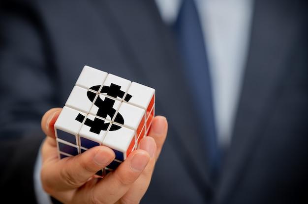 Handen van een zakenman die een kubus vasthoudt met een dollarindicatiepictogram zichtbaar.