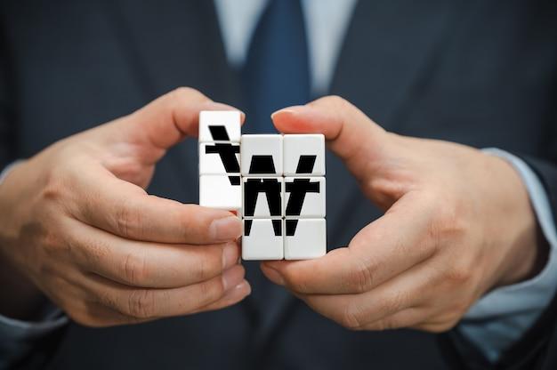 Handen van een zakenman die een kubus vasthoudt met een koreaans won-indicatiepictogram zichtbaar.