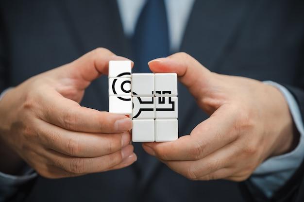 Handen van een zakenman die een kubus vasthoudt met een sleutelpictogram zichtbaar.
