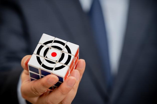 Handen van een zakenman die een kubus vasthoudt met een zakelijk doelpictogram zichtbaar.