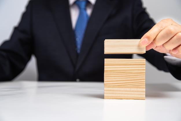 Handen van een zakenman die houten blokken op de lijst stapelt. bedrijfsconcept.