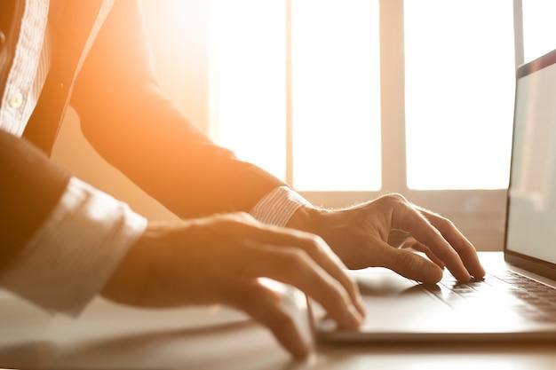 Handen van een zakenman die laptop op internet met behulp van