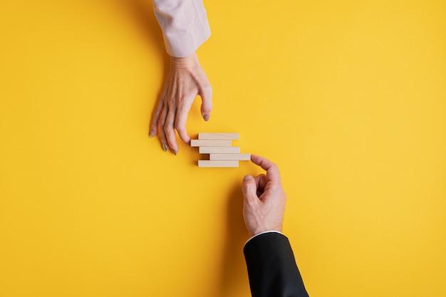 Handen van een zakenman en onderneemster die houten pinnen in een conceptueel beeld van bedrijfsstabiliteit en teamwerk stapelen.