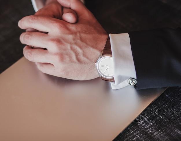 Handen van een zakenman in een horloge. jas, manchetknopen, laptop-heren set