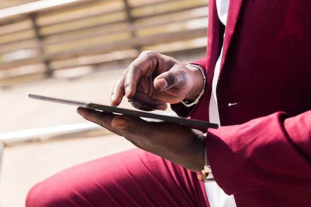 Handen van een zwarte man die buitenshuis een tablet gebruikt