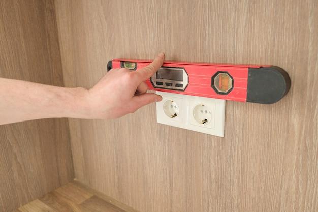Handen van elektricienarbeider die stopcontact installeren in meubilair