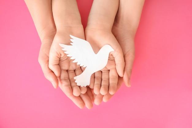 Handen van familie met papieren duif