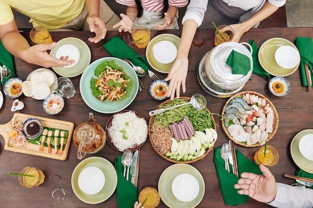 Handen van familieleden die eten en nieuws bespreken aan de eettafel, uitzicht vanaf de top