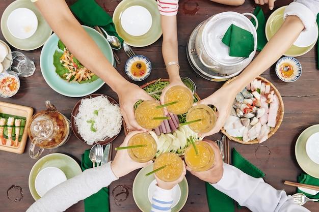 Handen van familieleden roosteren met glazen vers sap boven tafel met traditionele vietnamese gerechten