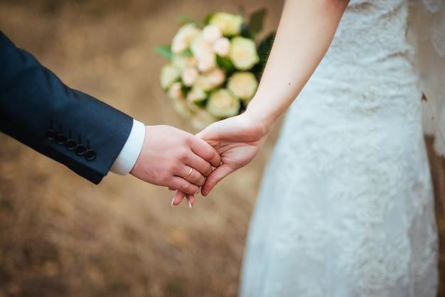 Handen van geliefden jonggehuwden met ringen