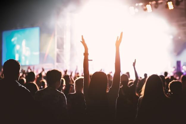 Handen van gelukkige mensen menigte plezier op het podium op zomer live rockfestival