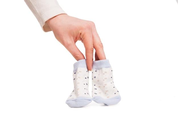 Handen van gelukkige zwangere vrouw die kleine sokken van kind over wit houdt