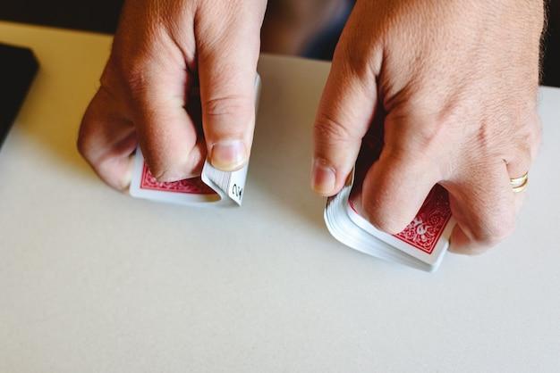 Handen van goochelaar die een pak pokerkaarten schuifelen voordat hij een trucje op een tafel doet.
