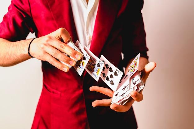 Handen van goochelaar doen trucs met een pak kaarten.