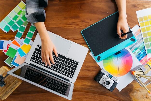 Handen van grafisch ontwerpers werken