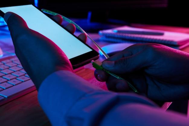 Handen van handen die mini usb-canble in smartphoneconnector zetten