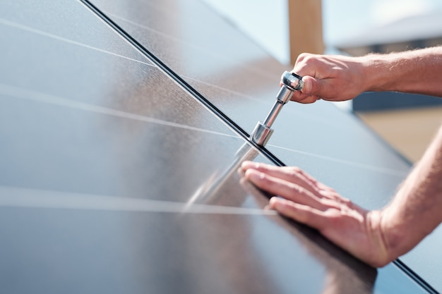 Handen van hedendaagse meester met schroef aanpassen of zonnepanelen installeren op het dak van het huis