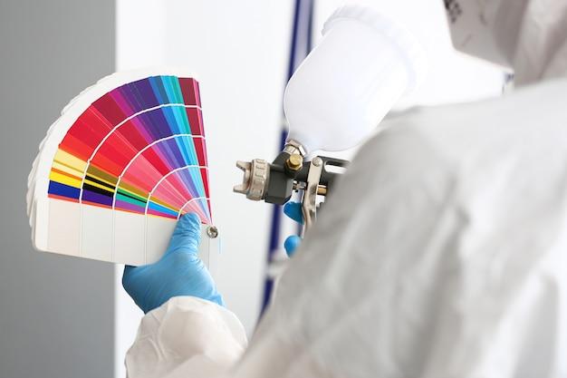 Handen van het airbrush van de werkmansholding en de kleurrijke toon van de fantail het plukken muur