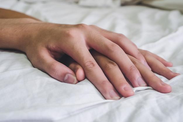 Handen van het geslacht van de paarminnaar op het bed, concept over liefde, geslacht en levensstijl.