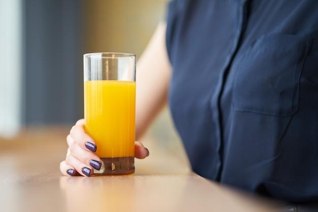 Handen van het glas van de vrouwenholding jus d'orange