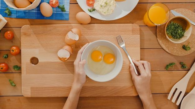 Handen van het jonge aziatische krakende ei van de vrouwenchef-kok in ceramische kom en het koken omelet