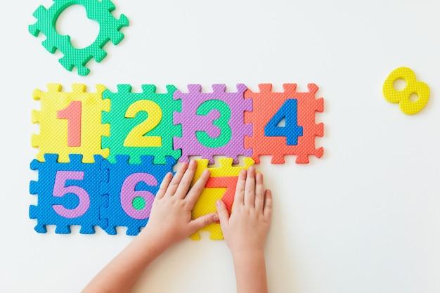 Handen van het kind spelen met getallen, eenvoudige vermenigvuldiging leren