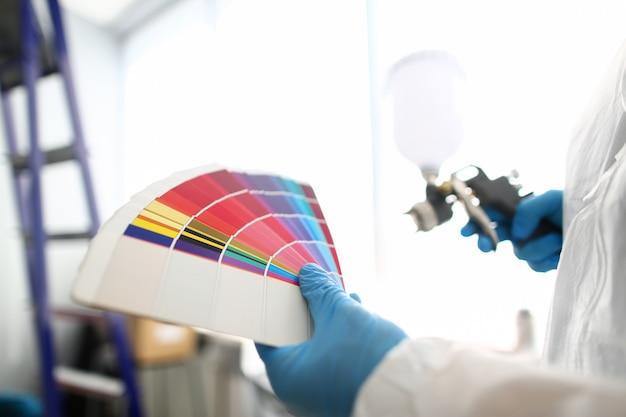 Handen van het luchtpenseel van de werkmansholding en kleurrijke fantail het plukken muurtoon om te schilderen