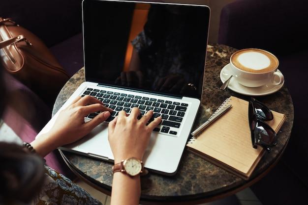 Handen van het onherkenbare vrouw typen op laptop in koffie