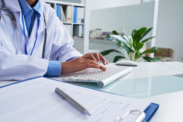 Handen van het onherkenbare vrouwelijke arts typen op toetsenbord in bureau
